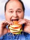 Photo of an obese man eating a large hamburger.